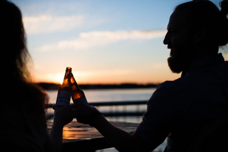 people in Germany cheering with a beer during sunset by the water