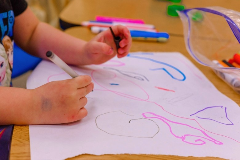 child scribbling on paper