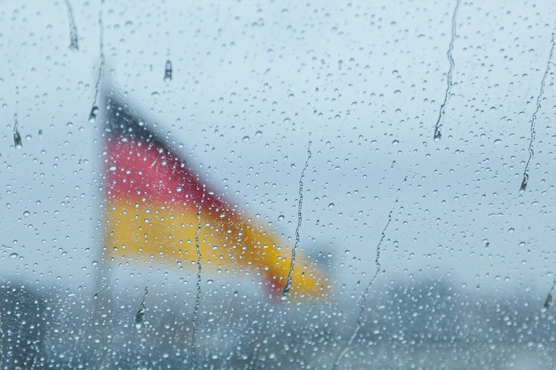 Rainy window with a German flag behind it