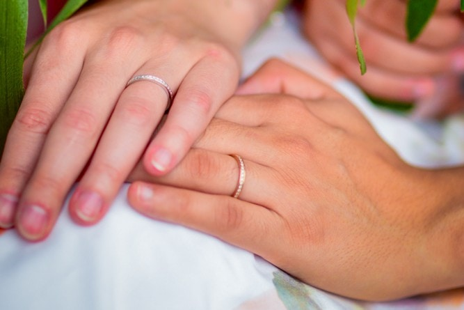 Picture of two hands with wedding rings holding each other